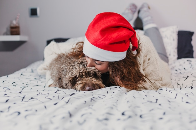 Young woman at home wearing a santa hat kissing her dog on bed. indoors. christmas concept