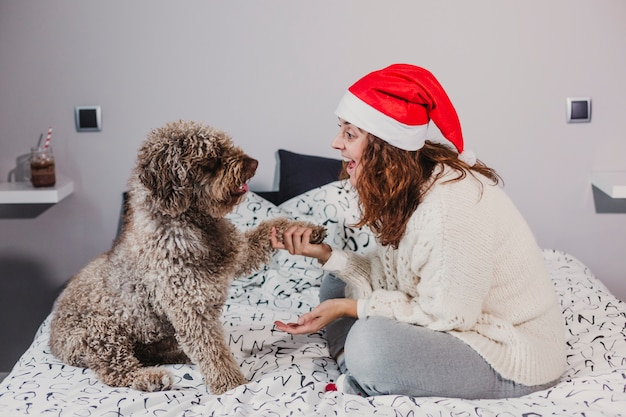 Young woman at home wearing a santa hat playing with her dog on bed. indoors. christmas concept
