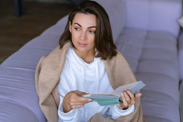 A young woman at home in a white hoodie on the couch wrapped herself in a warm blanket, reads a book
