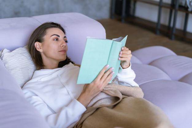 Una giovane donna a casa con una felpa bianca sul divano si è avvolta in una coperta calda, legge un libro
