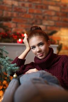 Giovane donna a casa con decorazioni natalizie