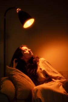 年轻女子在家里有神奇内部光在她附近