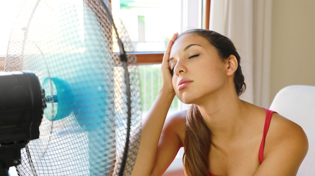 Young woman at home with working fan in hot summer day suffering heat.