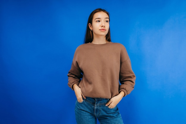 Young woman in hoodie posing in studio on blue background