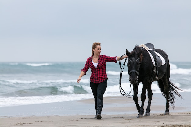 Young woman on a horse on the beach on a cloudy day