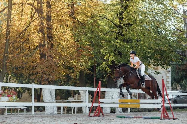 Молодая женщина-всадник-спортсменка на соревнованиях по конному спорту, перепрыгивая через препятствие