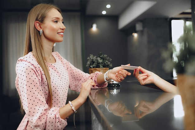Young woman hotel guest receiving key card from receptionist close up