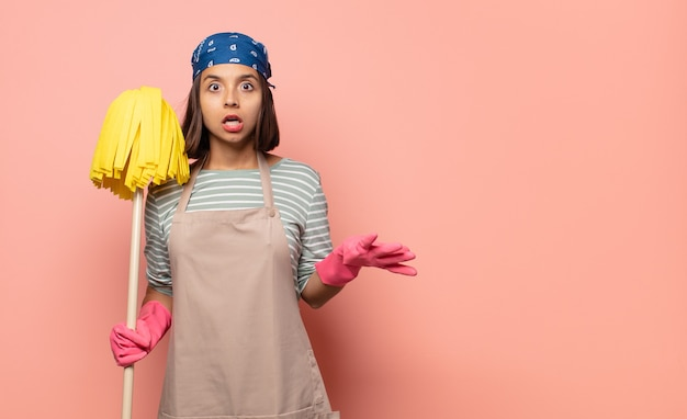 Young woman housekeeper feeling extremely shocked and surprised, anxious and panicking, with a stressed and horrified look