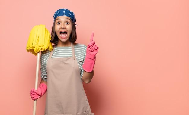 若い女性の家政婦は、アイデアを実現した後、幸せで興奮した天才のように感じ、元気に指を上げて、エウレカ!