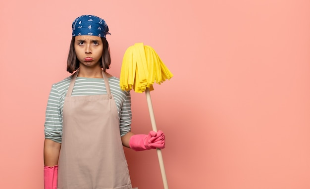 若い女性の家政婦は不幸な表情で悲しみと泣き言を感じています