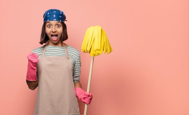 Молодая женщина-домработница потрясена, взволнована и счастлива, смеется и празднует успех, говоря