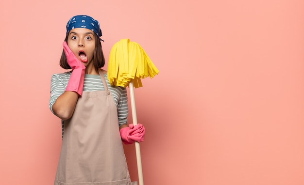 Young woman housekeeper feeling shocked and scared, looking terrified with open mouth and hands on cheeks
