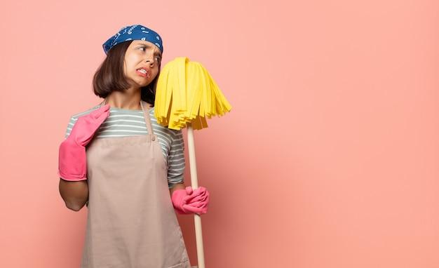 젊은 여성 가정부는 스트레스, 불안, 피곤하고 좌절감을 느끼고 셔츠 목을 당기고 문제로 좌절감을 느낍니다.
