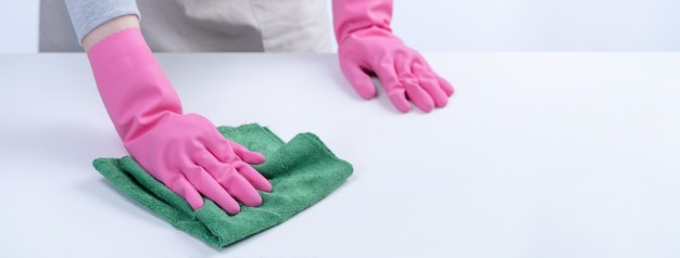 Молодая домработница в фартуке протирает поверхность стола влажной тряпкой, распыляя средство для чистки бутылок, чтобы предотвратить распространение болезни