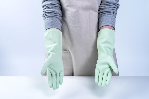 Молодая домработница в фартуке носит зеленые перчатки, чтобы убрать стол, концепция предотвращения вирусной инфекции на белом фоне, крупным планом.