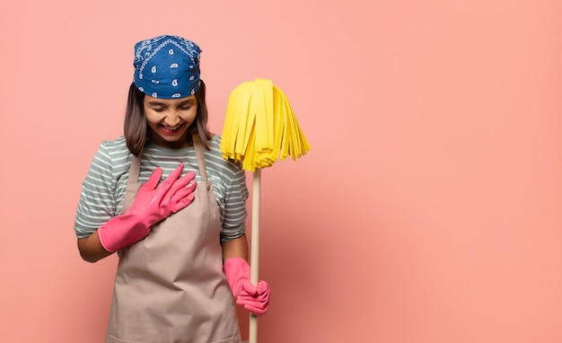 Young woman housekeeper laughing out loud at some hilarious joke, feeling happy and cheerful, having fun