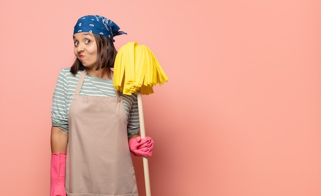 Young woman housekeeper shrugging, feeling confused and uncertain, doubting with arms crossed and puzzled look