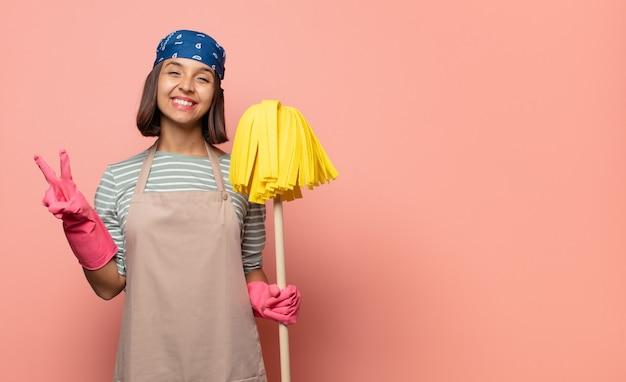 若い女性の家政婦は笑顔で幸せそうに見え、のんきで前向きで、片手で勝利または平和を身振りで示す