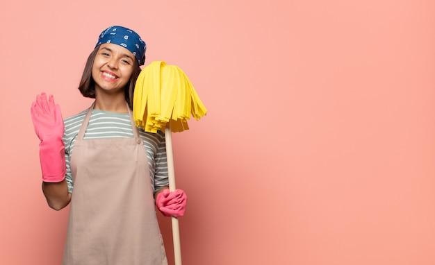 Молодая женщина-домработница счастливо и весело улыбается, машет рукой, приветствует и приветствует вас или прощается