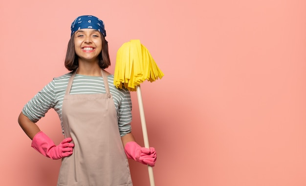 Young woman housekeeper smiling happily with a hand on hip and confident, positive, proud and friendly attitude