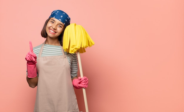 Young woman housekeeper smiling proudly and confidently making number one pose triumphantly, feeling like a leader