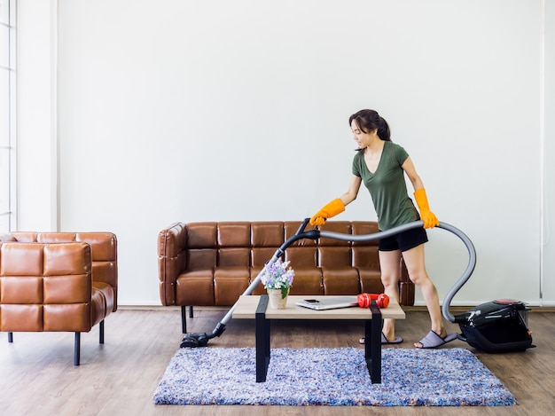 Young woman, housewife in casual clothes and orange rubber gloves using vacuum cleaner to clean floor in living room near brown leather sofa and table on white wall with copy space.