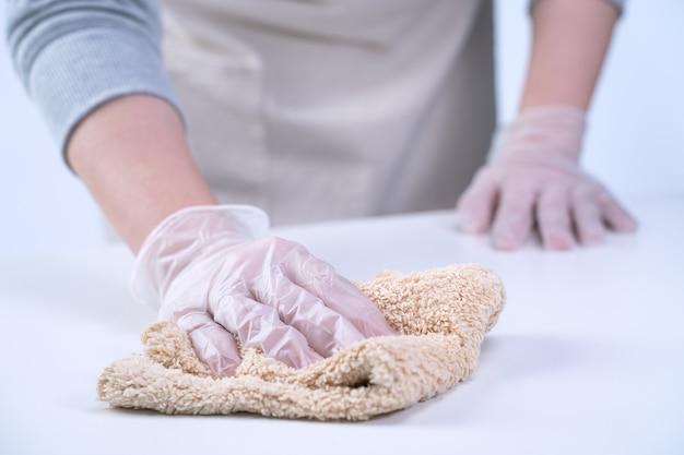 젊은 여성 주부는 젖은 걸레, 항균제, 클로즈업, 생활 방식으로 감염 확산을 막기 위해 집 테이블 표면을 닦고 청소하고 있습니다.