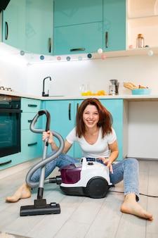 若い女性主婦は掃除機で遊ぶ。楽しいアパートの掃除