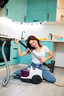Young woman housewife plays with a vacuum cleaner. fun apartment cleaning