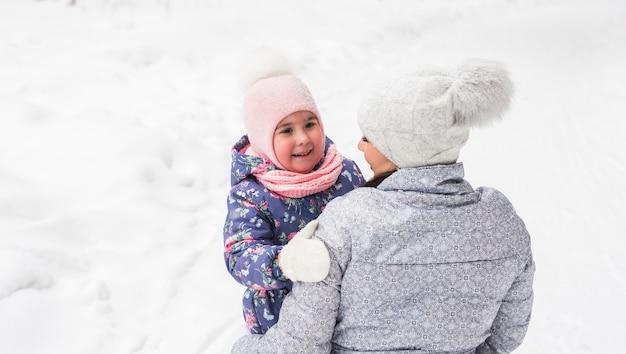 若い女性は公園で小さな幸せな娘を抱きしめます