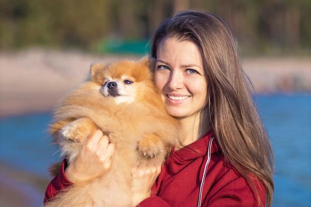 Молодая женщина обнимает собаку померанский шпиц на руках. уход за домашними животными, усыновление.
