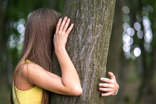 나무를 포옹하는 젊은 여자