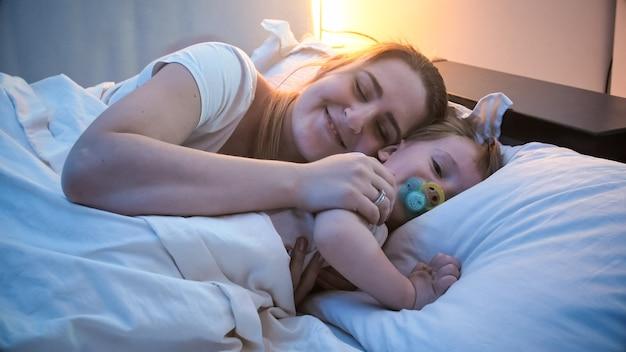 포옹 하 고 밤에 잠자리에 가기 전에 그녀의 작은 유아 아들을 껴 안은 젊은 여자.