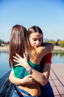 若い女性を抱き締めると彼女の最高の女性の友人をサポート