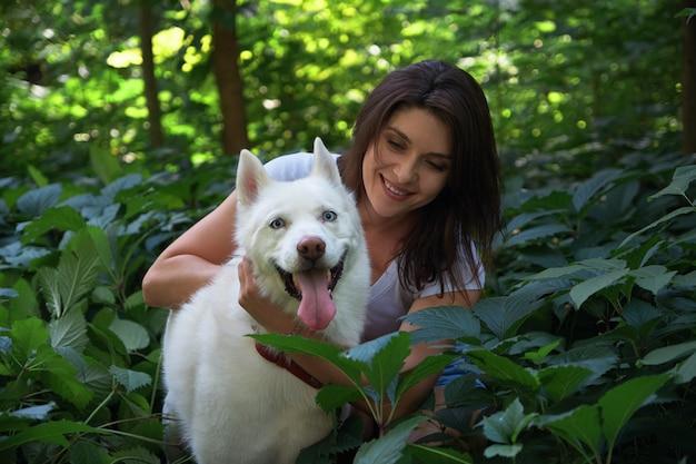 Молодая женщина обнимает собаку