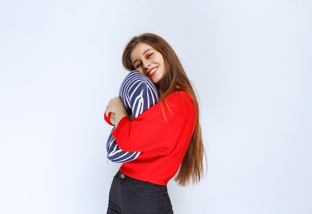 Young woman hugging a blue striped pillow and sleeping.