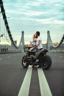 Young woman hugging cute man in stylish black leather jacket, sitting on sports motorcycle on the bridge in the city on sunset and kissing.