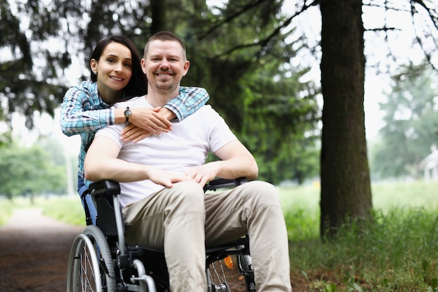 Young woman hugging disabled man in wheelchair in park
