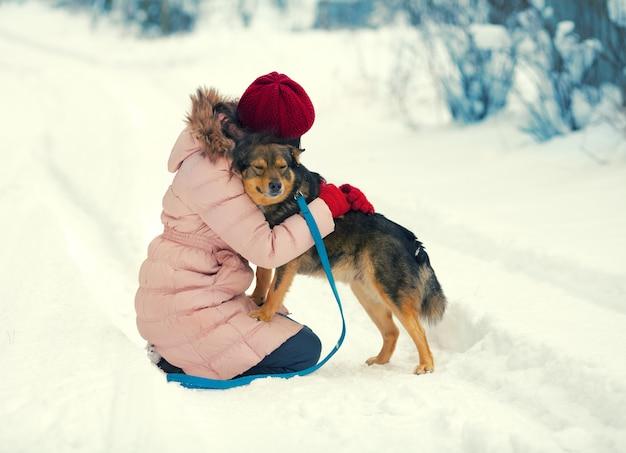 Молодая женщина обнимает собаку на заснеженной дороге