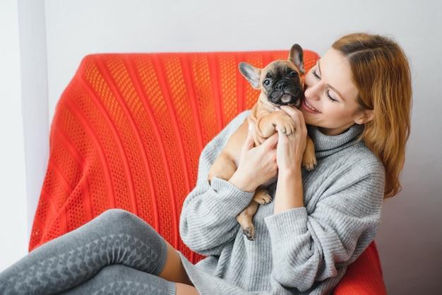 Молодая женщина обнимает свою милую маленькую собачку дома, сидя на диване
