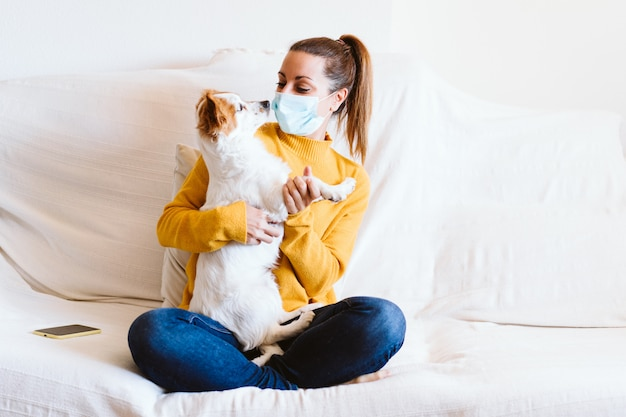 Young woman hugging her cute small dog at home, sitting on the couch, wearing protective mask. stay home concept during coronavirus covid-2019