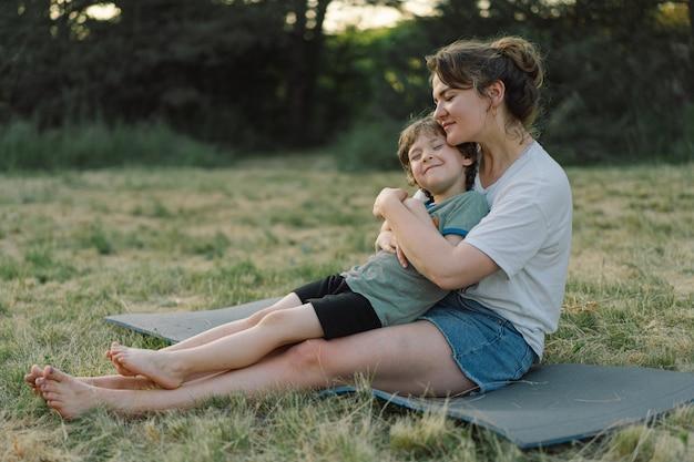 초원에서 햇볕이 잘 드는 그녀의 어린 아들을 껴안고 젊은 여자