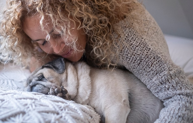 ベッドで寝ている間に彼女の愛犬を抱き締める若い女性。一緒にベッドで寝ている女性と彼女の犬のパグのクローズアップ。自宅の居心地の良いベッドで寝ている女性と愛犬