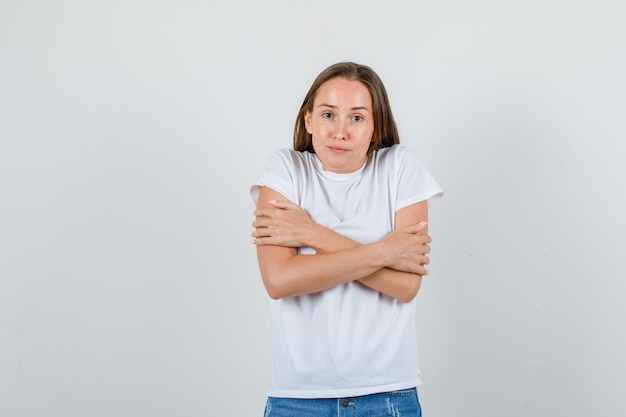 Young woman hugging herself and feeling cold in white t-shirt, shorts front view.