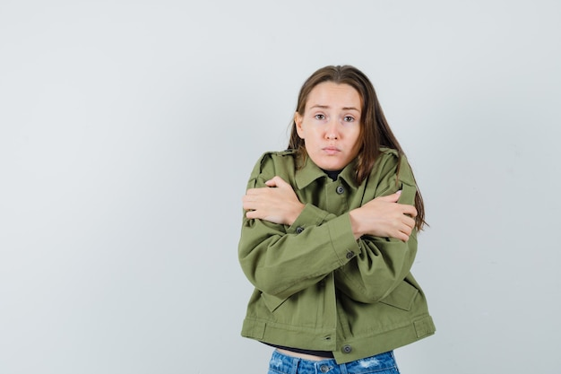 Giovane donna che si abbraccia in giacca verde e che sembra eccitata, vista frontale.