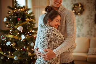 Young woman hugging man near decorated fir tree
