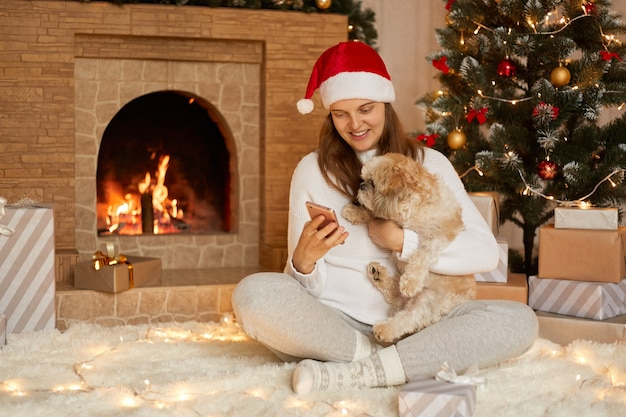 Young woman hugging pekingese dog at christmas time, holding phone in hands and looking at device's screen with smile, female with crossed legs near fireplace and x-mas tree.