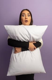 枕を抱き締める若い女性が混乱して心配している