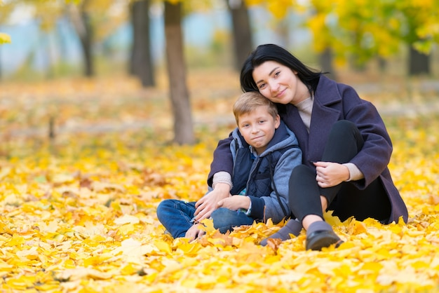 Young woman hugging teenage boy in park sitting on the ground covered with bright yellow leaves in autumn, looking at camera. full-length portrait with copy space