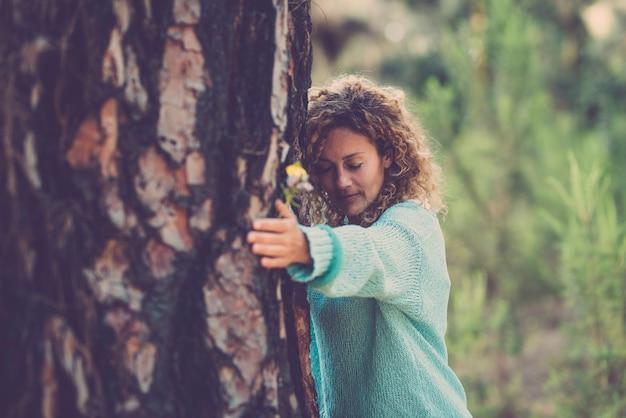 森の中で目を閉じて木を抱き締める若い女性。愛情と思いやりで木を抱きしめる美しい白人女性。森の樹皮に触れる思いやりのある女性